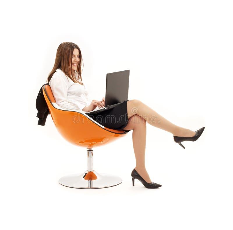 Empresaria con la computadora portátil en o foto de archivo