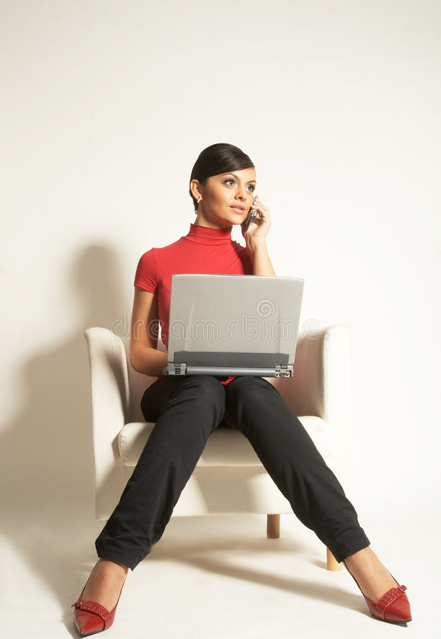 Empresaria con la computadora portátil y el teléfono foto de archivo