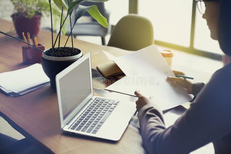 Empresaria con la hoja de papel de los documentos en la oficina moderna del desván, trabajando en el ordenador portátil Funcionam fotos de archivo libres de regalías