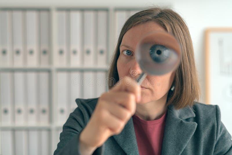 Empresaria con la lupa que hace auditar financiero del negocio imagenes de archivo