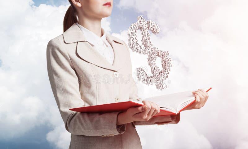 Empresaria con la muestra de dólar sobre el libro abierto foto de archivo libre de regalías
