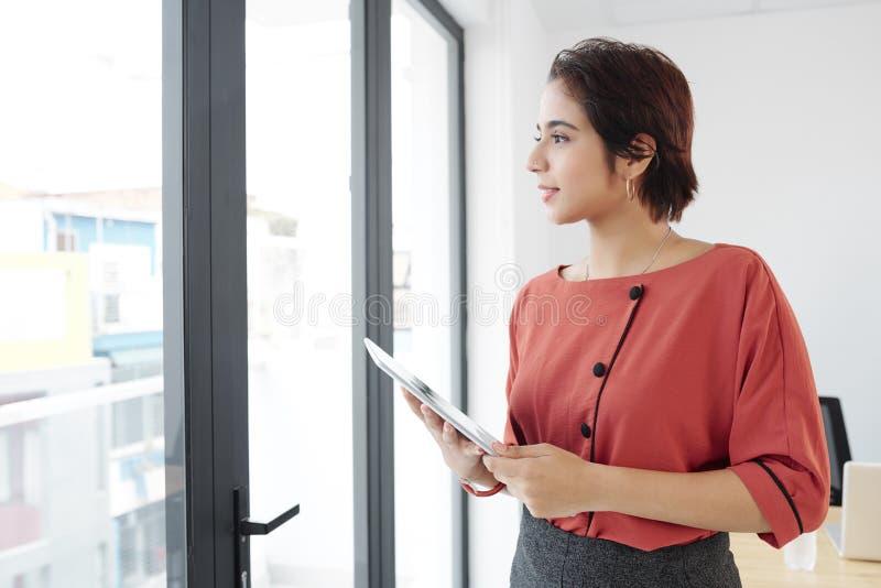 Empresaria con la situación de la PC de la tableta en la oficina foto de archivo libre de regalías