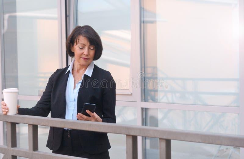 Empresaria con un smartphone y taza de café imagen de archivo