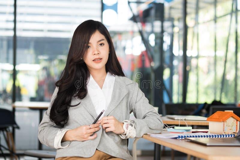 Empresaria confiada que se sienta en la oficina entrepre femenino joven foto de archivo