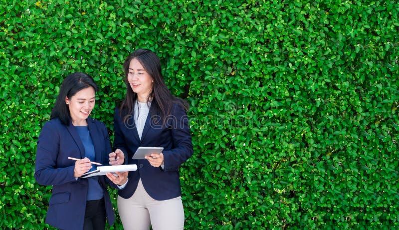 Empresaria de dos asiáticos que toma sobre trabajo fuera de la oficina en el gree fotos de archivo libres de regalías