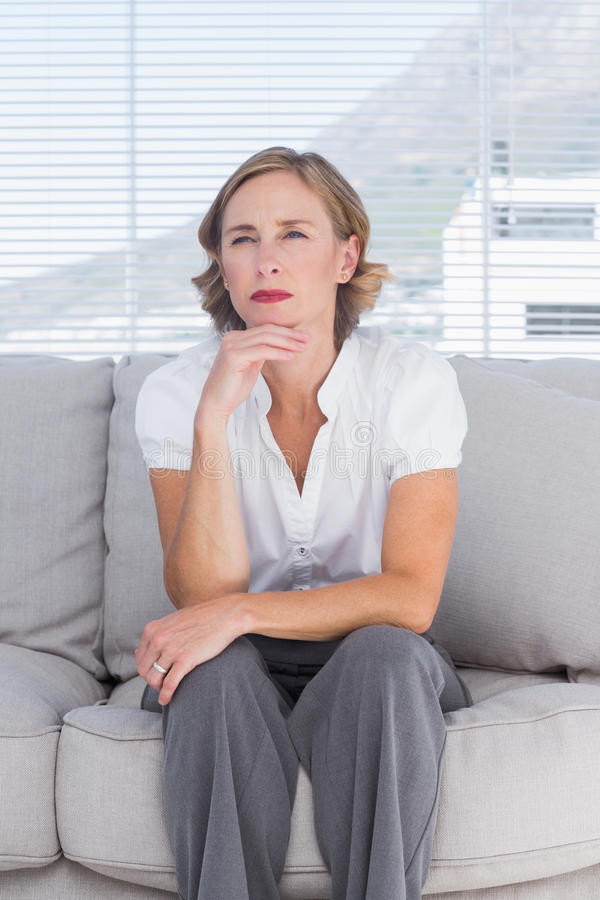 Empresaria de pensamiento que se sienta en el sofá imagen de archivo