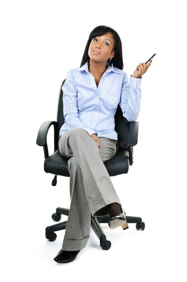 Empresaria de pensamiento que se sienta en silla de la oficina fotos de archivo
