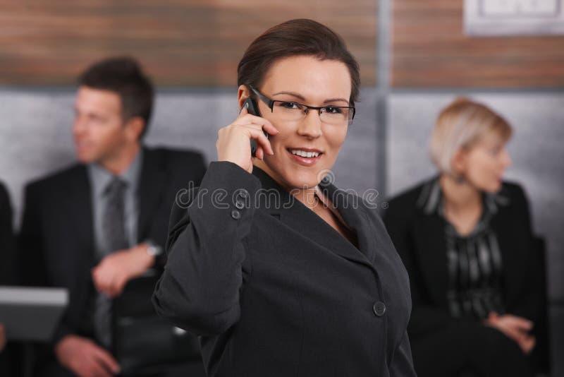 empresaria del Mediados de-adulto que habla en móvil foto de archivo