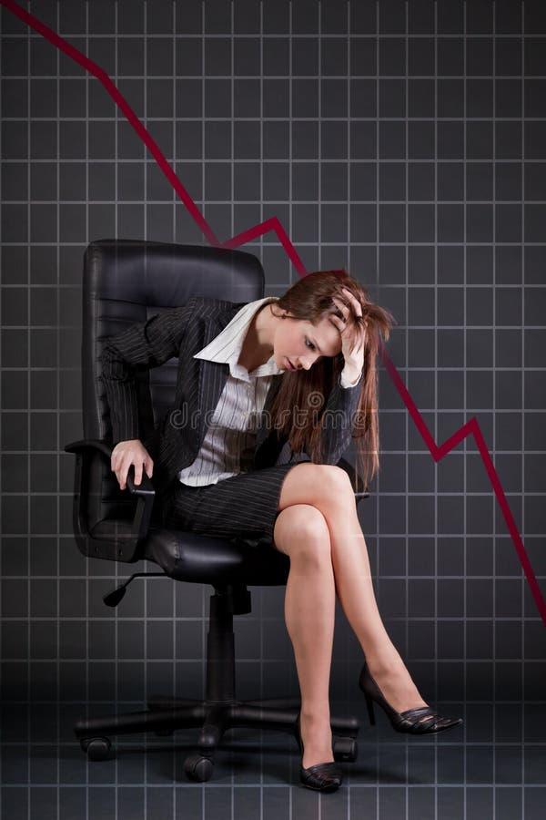 Empresaria deprimida que se sienta en butaca de la oficina imagen de archivo