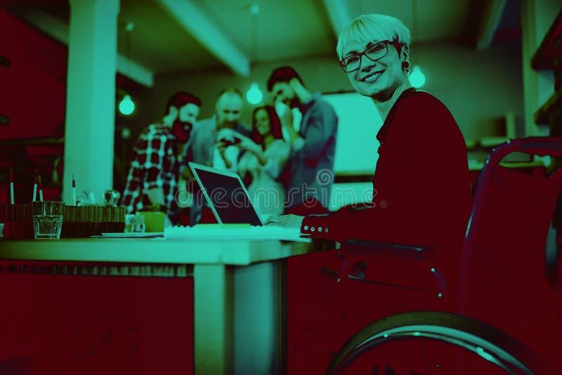 Empresaria discapacitada feliz que usa el ordenador portátil en el escritorio imagenes de archivo