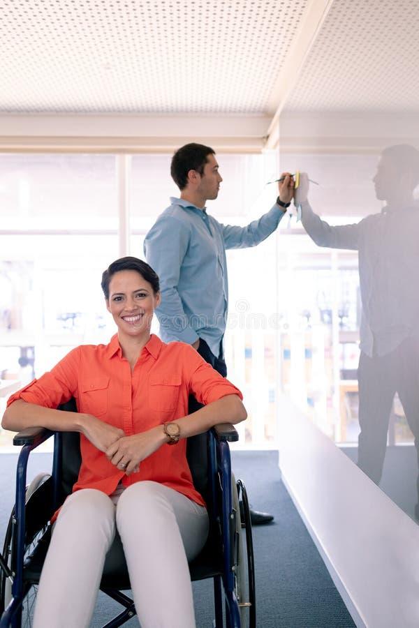 Empresaria discapacitada que mira la cámara mientras que su escritura del colega en el tablero de cristal en oficina imagenes de archivo