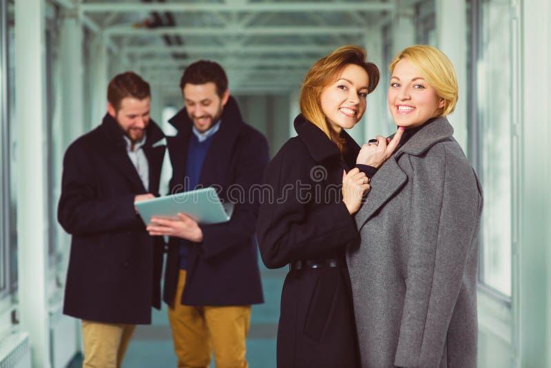 Empresaria dos que mira en usted en pasillo con los colegas el fondo fotos de archivo