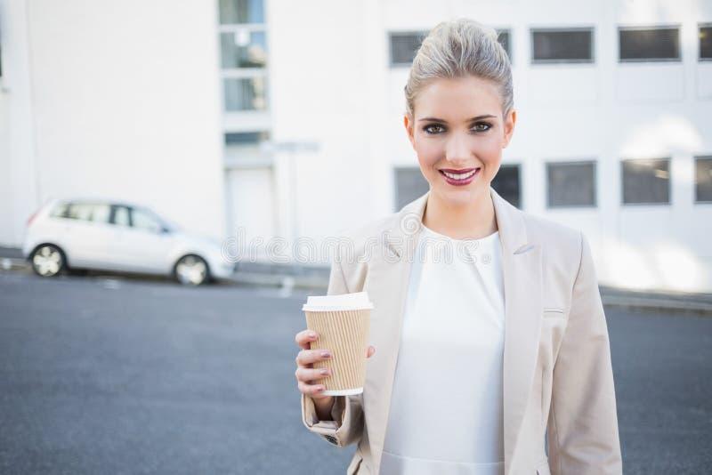 Empresaria elegante alegre que sostiene el café imagen de archivo