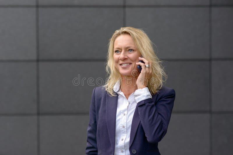 Empresaria elegante que habla en un móvil imagen de archivo