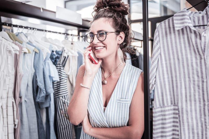 Empresaria elegante que lleva los accesorios hermosos que tienen conversación telefónica imagen de archivo