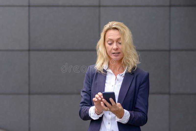 Empresaria elegante que manda un SMS en un móvil foto de archivo