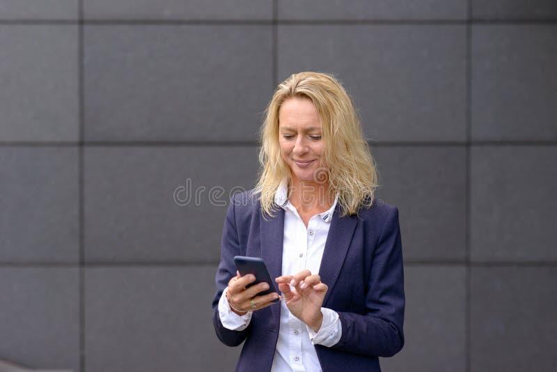 Empresaria elegante que manda un SMS en un móvil fotos de archivo libres de regalías