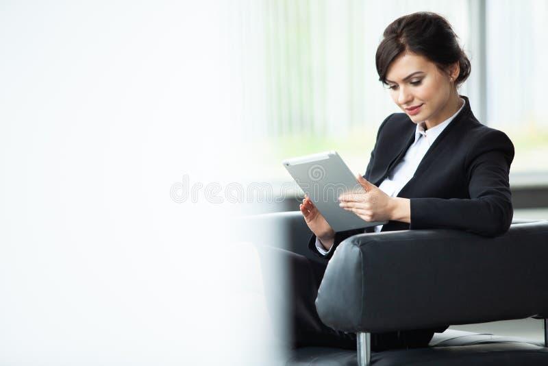 Empresaria elegante que se sienta en el sofá usando la PC de la tableta en la oficina foto de archivo