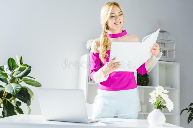 empresaria elegante que trabaja con los documentos y el ordenador portátil imágenes de archivo libres de regalías