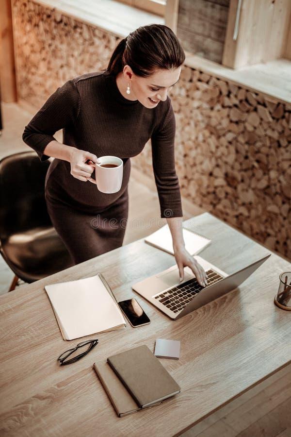 Empresaria embarazada alegre que trabaja en su oficina fotos de archivo libres de regalías