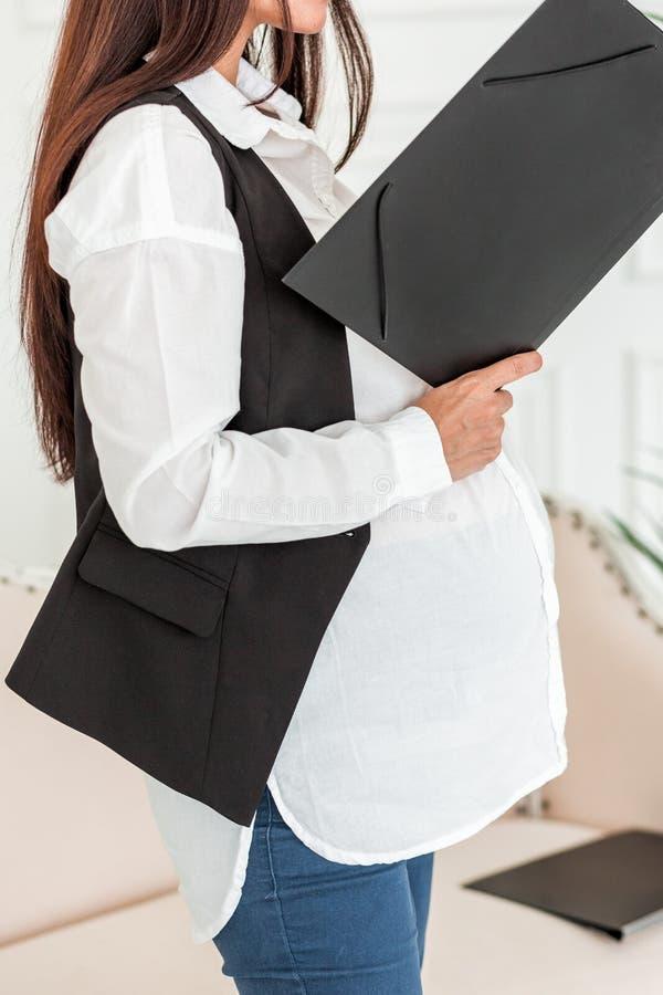 Empresaria embarazada en el trabajo en una oficina que lee un documento fotos de archivo