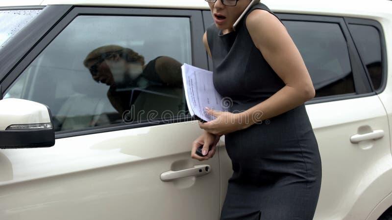 Empresaria embarazada ocupada que camina al coche, dolor agudo de sensación en vientre, salud imagen de archivo libre de regalías