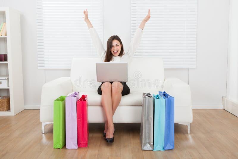 Empresaria emocionada con el ordenador portátil que hace compras en línea en el sofá fotos de archivo