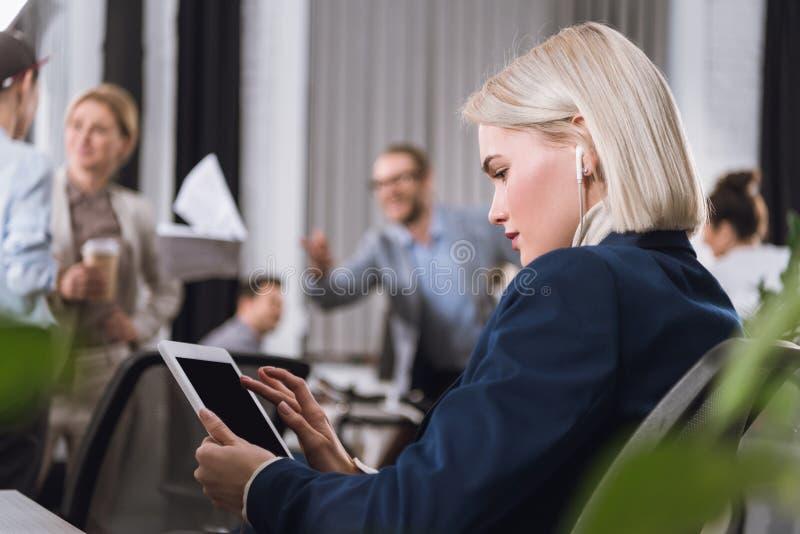Empresaria en auriculares con la tableta imagen de archivo