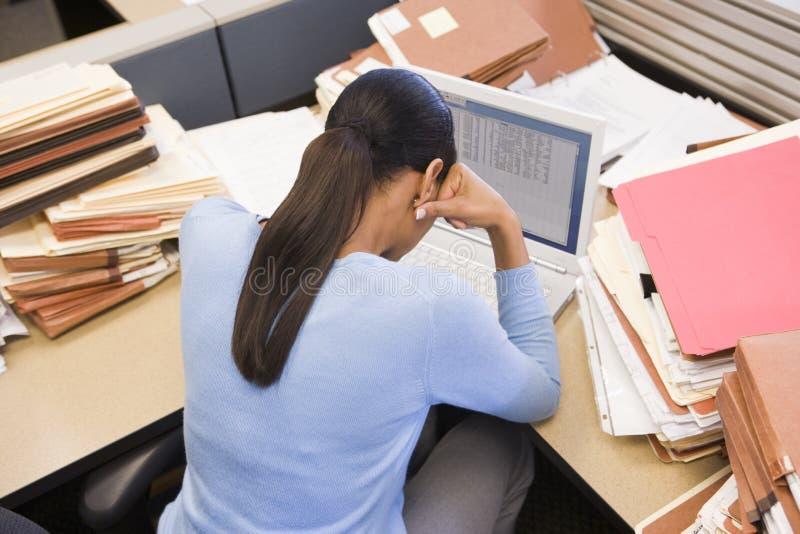 Empresaria en cubículo con la computadora portátil foto de archivo libre de regalías