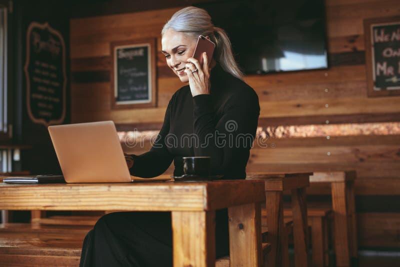 Empresaria en el café que hace una llamada de teléfono y que usa el ordenador portátil fotos de archivo