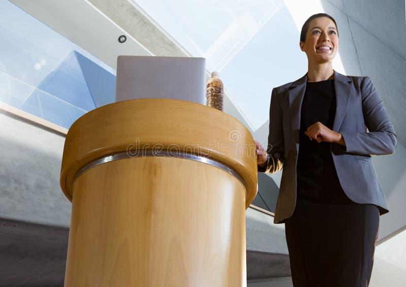 Empresaria en el podio que habla en la conferencia con el fondo arquitectónico de la perspectiva foto de archivo libre de regalías