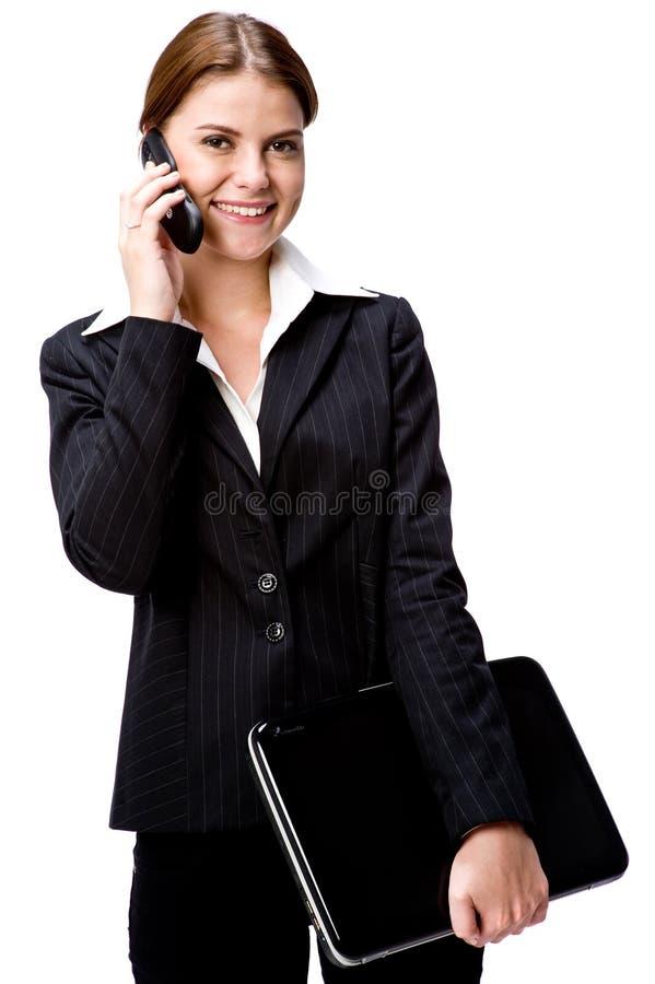 Empresaria en el teléfono con la computadora portátil imagen de archivo libre de regalías
