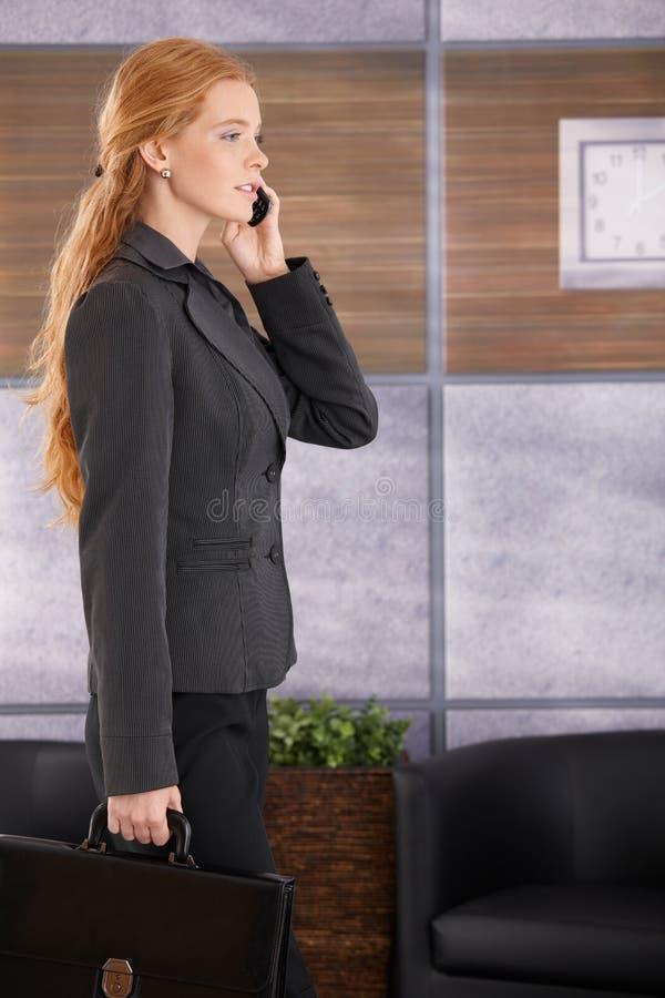 Empresaria en el teléfono que llega a la oficina imágenes de archivo libres de regalías