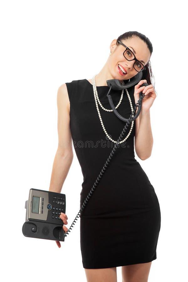Empresaria en el vestido negro que sostiene el teléfono y tal morenos imagen de archivo libre de regalías