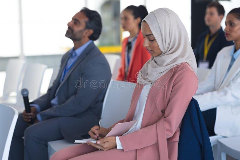 Empresaria en hijab que escribe en la libreta en un seminario del negocio fotografía de archivo libre de regalías
