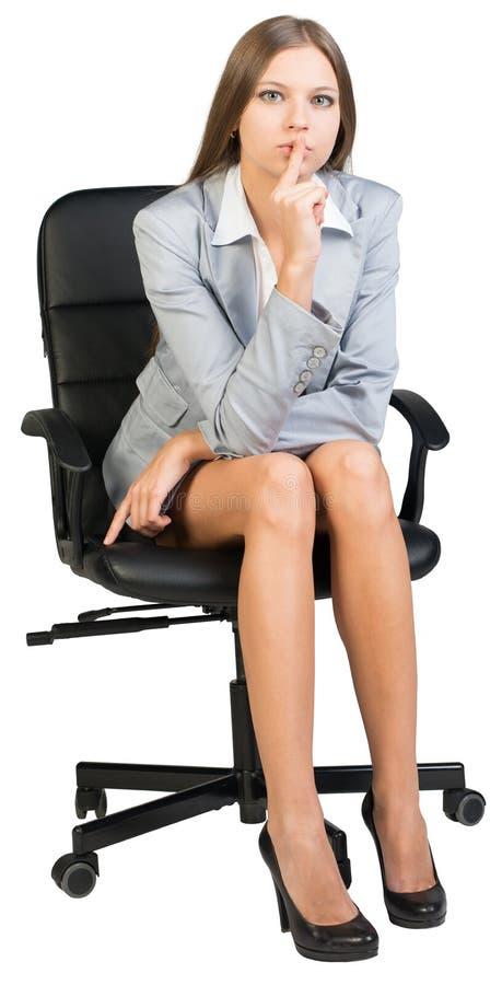 Empresaria en la silla de la oficina que sostiene el finger a fotografía de archivo libre de regalías