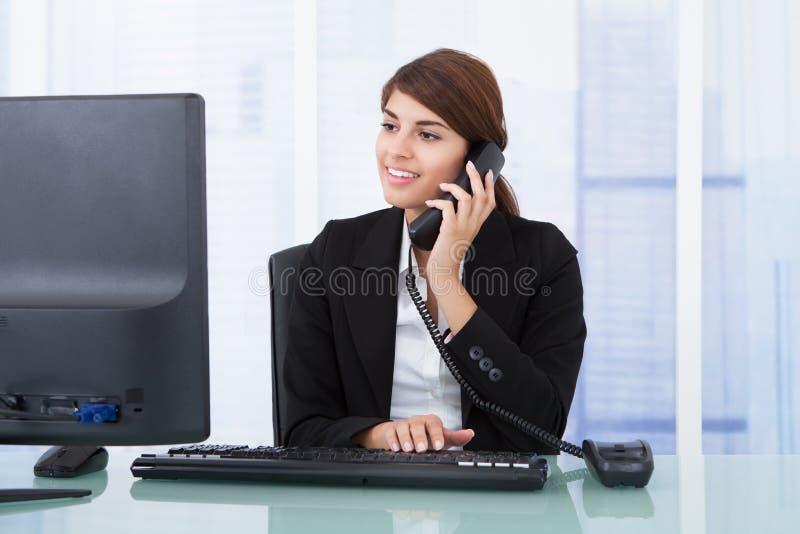 Empresaria en llamada mientras que usa el ordenador en el escritorio imagen de archivo libre de regalías