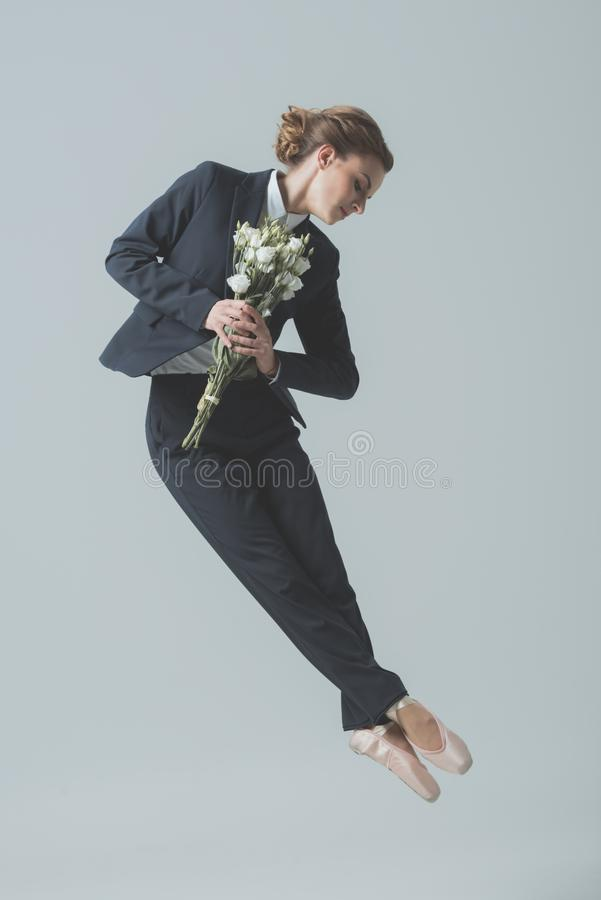 empresaria en los zapatos del traje y de ballet que saltan con el ramo de flores fotografía de archivo libre de regalías
