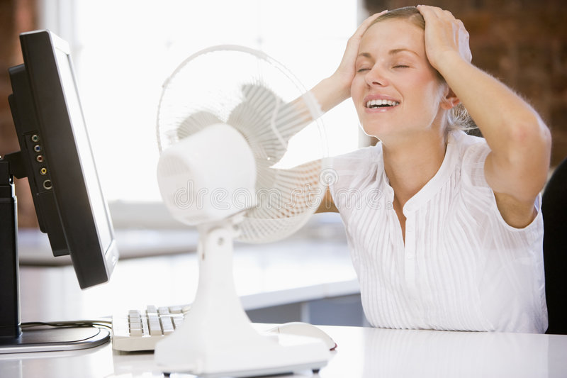 Empresaria en oficina con el ordenador y el ventilador foto de archivo libre de regalías