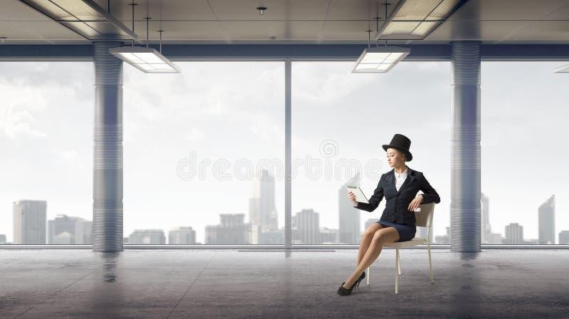 Empresaria en silla en oficina foto de archivo