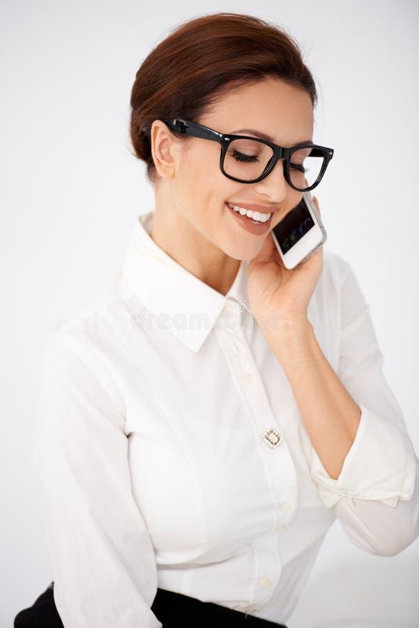 Empresaria en vidrios que charla en un móvil foto de archivo libre de regalías
