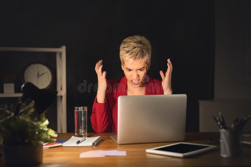 Empresaria enojada en su oficina en la noche que trabaja tarde fotografía de archivo libre de regalías
