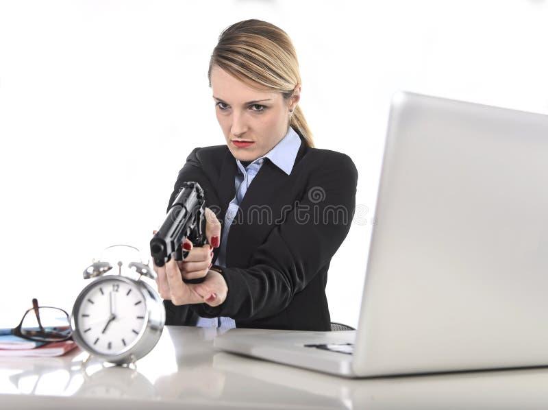Empresaria enojada furiosa que trabaja señalando el arma al despertador adentro de concepto del tiempo imagenes de archivo