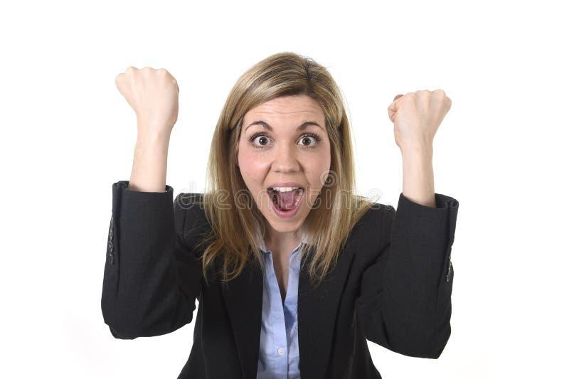 Empresaria feliz atractiva que plantea gesticular con el puño emocionado en éxito empresarial imagen de archivo libre de regalías