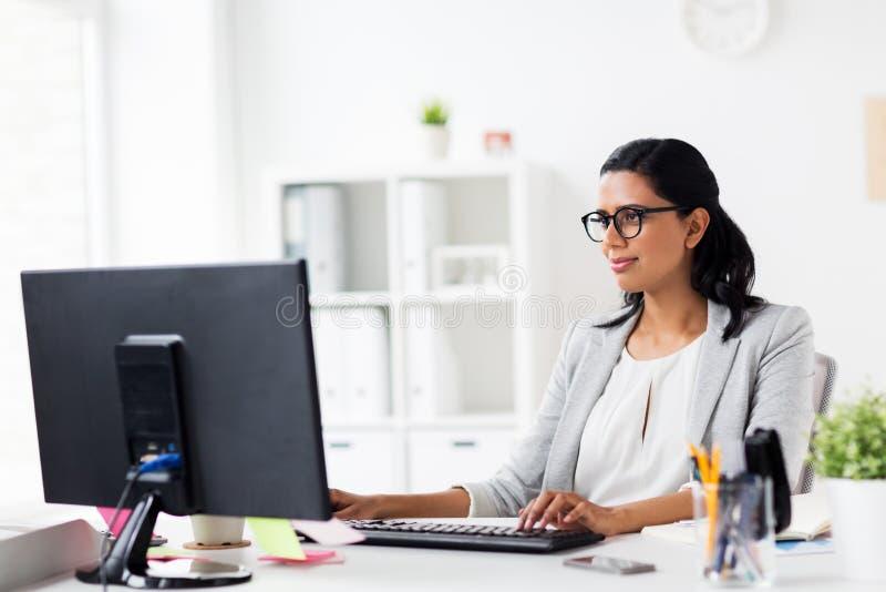 Empresaria feliz con el ordenador en la oficina fotos de archivo