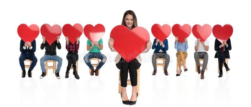 Empresaria feliz delante de un equipo grande que lleva a cabo el corazón imagenes de archivo
