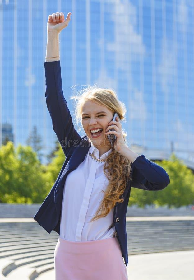 Empresaria feliz joven con el brazo aumentado que habla en el teléfono en la calle que recibe buenas noticias imágenes de archivo libres de regalías