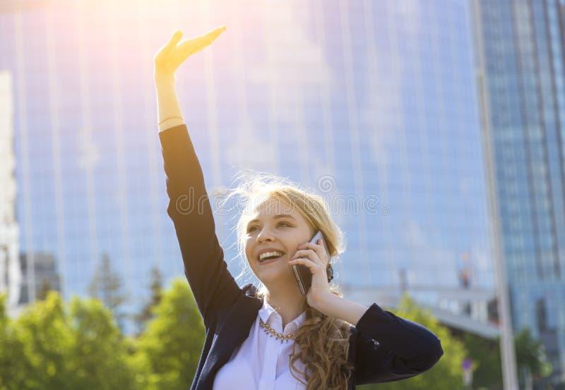 Empresaria feliz joven con el brazo aumentado que habla en el teléfono en la calle que recibe buenas noticias Señora con la celeb imagen de archivo libre de regalías
