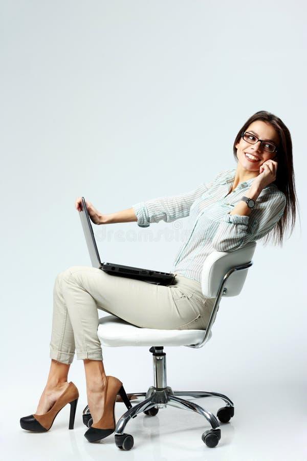 Empresaria feliz joven que se sienta en la silla con el ordenador portátil fotos de archivo
