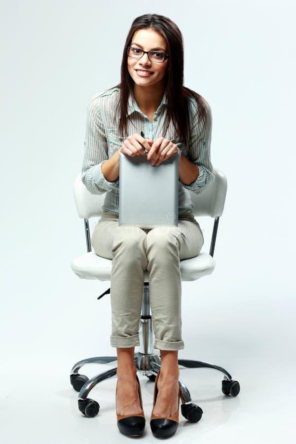 Empresaria feliz joven que se sienta en silla de la oficina y que sostiene la tableta imagen de archivo